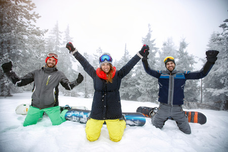 Female with two male snowboarders kneeling on snow with raised hands