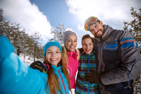 Happy children with parents on skiing in mountain