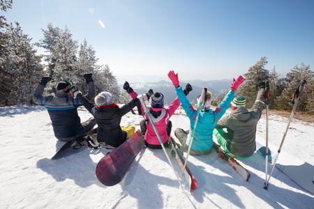 Happy skiers sitting on snow in mountain with hands up, back view Banque d'images