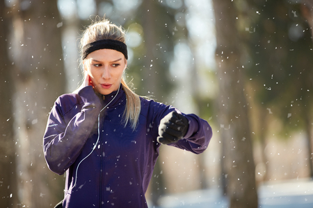 Female on pause from cardio training controls pulse outdoor
