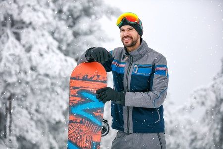 Young man with board to ski terrain