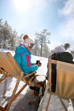 Back view of two female in sunbed talking and resting from skiing Banque d'images
