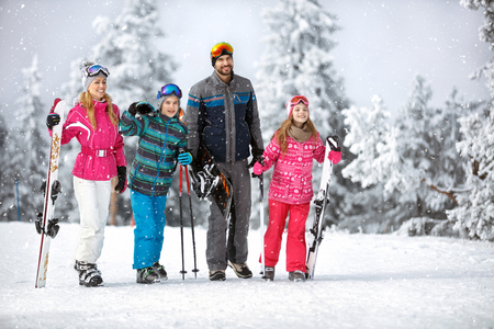 Happy family at winter holiday going to ski terrain with ski equipment  Stock fotó