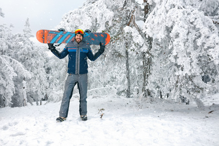 Male snowboarder with board going to ski terrain  Banque d'images