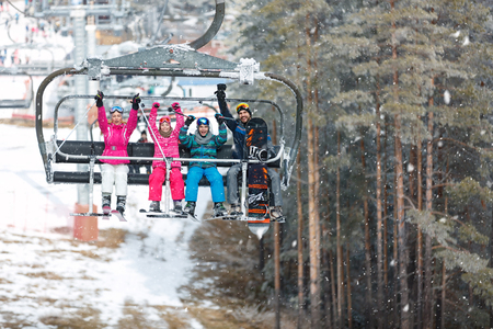 Cheerful parents with male and female child in chair lift climb up on ski terrain Banque d'images