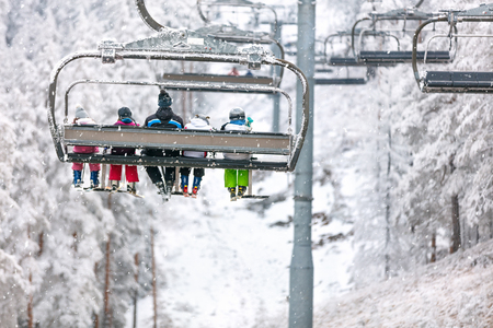 Group of skiers on ski lift, back view
