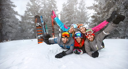 Happy group of skiers lying on snow with raised hands