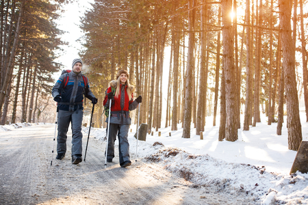Young mountaineers couple walking with hiking sticks on mountain Banque d'images