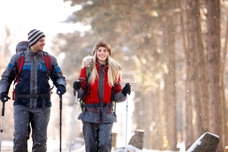 Male and female young hikers walking in snowy nature