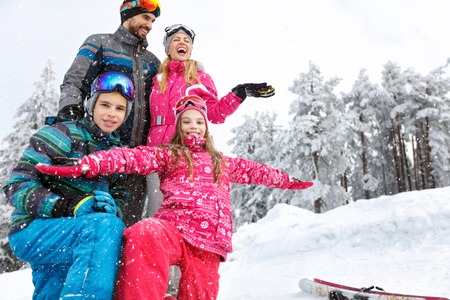 Happy family with children enjoying on winter vacation in snowy nature