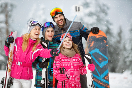 happy family taking selfie photo while skiing in snow