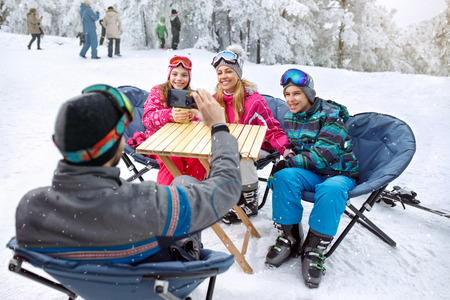 Father making photo of his cheerful family in cafe on ski terrain
