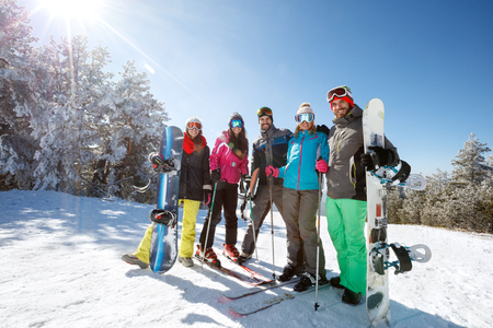 Group of happy skiers and boarders together on mountain