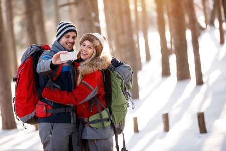Boy and girl taking photo while hiking in snowy nature Banque d'images