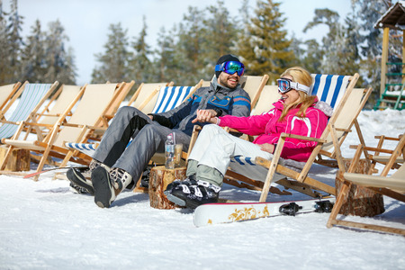 Skiers couple in sun lounger relax and enjoy on sun  Stock Photo