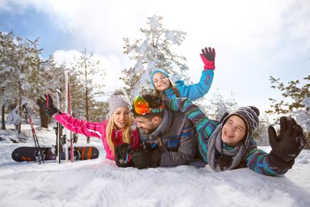 Cheerful family enjoying on snow on winter vacation