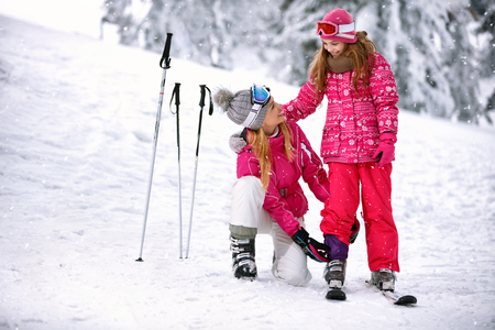 Young mother fixing pants to daughter on ski terrain