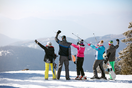 Skiers group in mountain with ski sticks up, back view