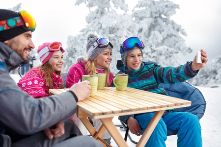 Happy boy making selfie with family in cafe on ski terrain