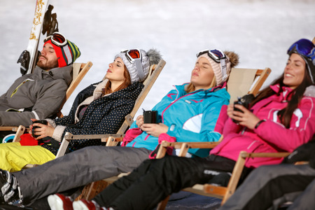 Skiers group resting and sunbathing in sunbed in cafe on ski terrain