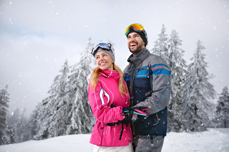 Smiling couple happy together on mountain for winter vacation