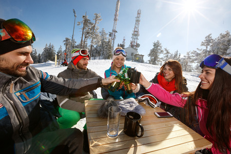 Happy skiers group toasts with drinks in cafe on ski terrain