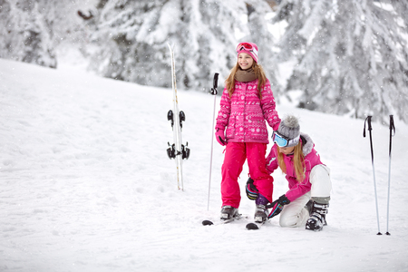 Mother helps her daughter to properly puts ski shoes on skis on ski terrain