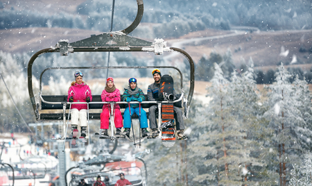Parents with children in the ski lift climbs on the snowy ski terrain Stock Photo