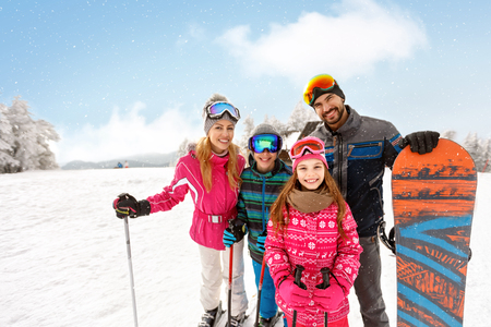 Skiers family together on skiing on ski terrain