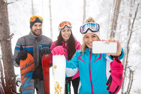 Young male and female snowboarders taking selfie together Banque d'images
