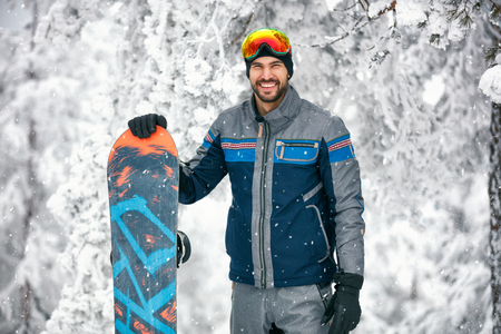 Cheerful snowboarder with board on mountain