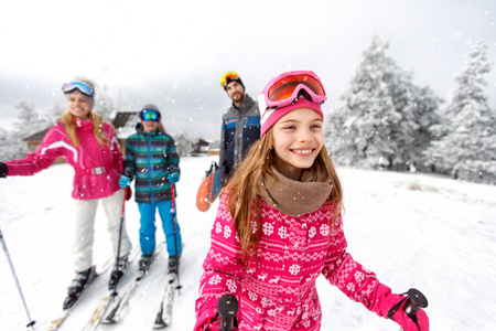 Cute girl skier skiing with family on mountain  Banque d'images