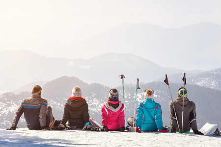 Skiers looking mountains landscape while sitting on snow together, back view