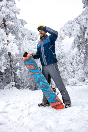 Male snowboarder holding snowboard and looking at distance on ski terrain