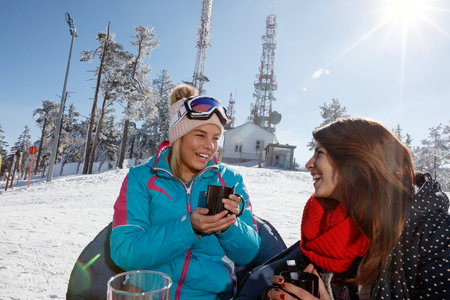 Young women drinking tea in cafe outdoor on skiing Banque d'images