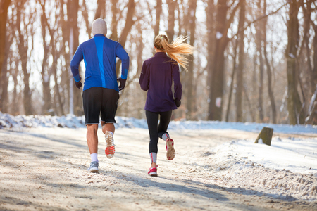 winter Couple jogging in nature together, back view