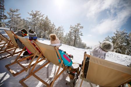 Back view of skiers sunbathing in sun bad on ski terrain  Zdjęcie Seryjne