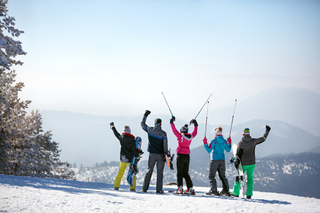 Back view of skiers with ski sticks up on the top of the mountain 写真素材