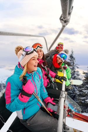 cheerful young friends skiers on ski lift ride up on ski slope at snowy day Stock Photo