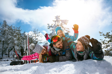 Young smiling family on winter vacation - Ski, snow, sun and fun