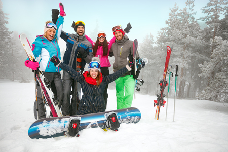 Group of cheerful friends skiers and snowboarders having fun on snowbound winter forest Standard-Bild