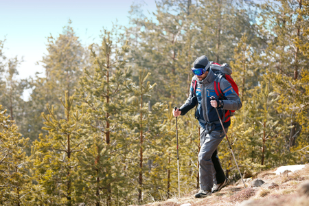 Active young man hiking in forest mountains