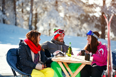 Smiling friends spending time together and drink after skiing in cafe at ski resort in mountains Banco de Imagens