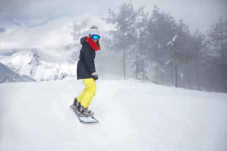 Female snowboarder on snowboard on cold snowy mountain