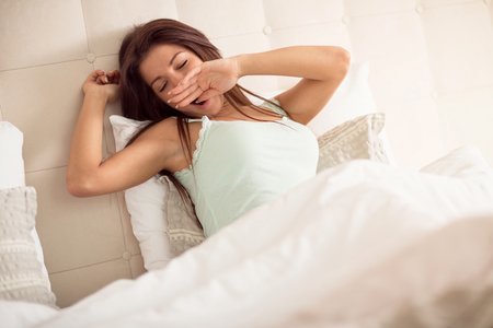 Nice girl yawning while walking up in bed Stock Photo - 94401977