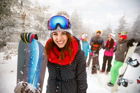 Sporty female holds snowboard in mountains on winter holiday