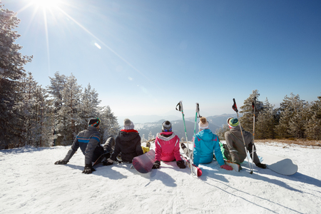 Skiers sitting on snow and looking landscape on skiing in mountain, back view  Zdjęcie Seryjne