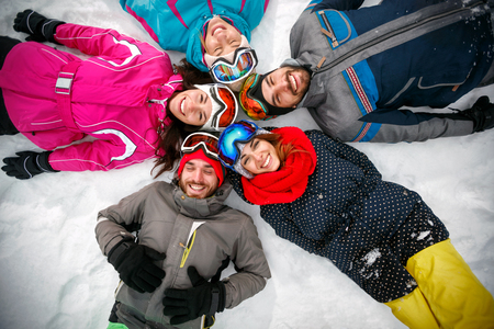 young skiers lying on snow and having fun top view