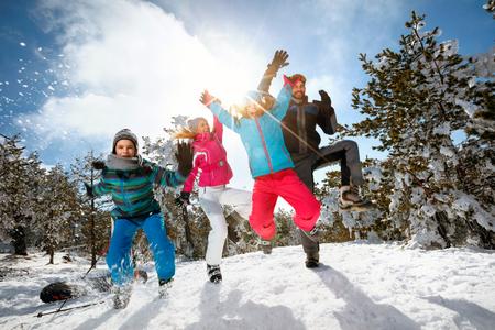 Gelukkig gezin met kinderen hoogspringen op winterdag op skivakantie en plezier maken Stockfoto