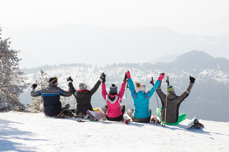 Skiers group looking beautiful landscape while sitting on snow in mountain, back view
